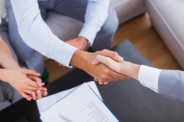 Salesman shaking hands with client with contract on the coffee table-1
